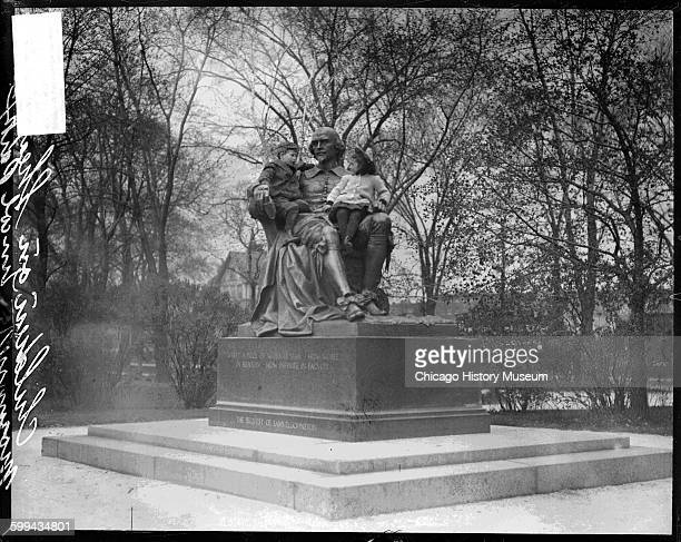 Portrait of children sitting in the lap of the William Shakespeare statue located at the foot of West Belden Avenue in Lincoln Park in the Lincoln...