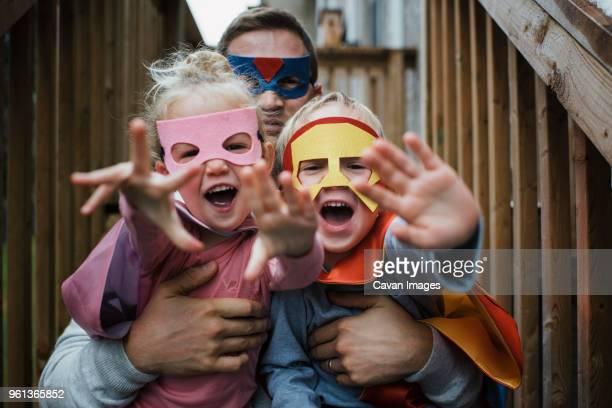 portrait of children with father in superhero costumes - disfrazarse fotografías e imágenes de stock