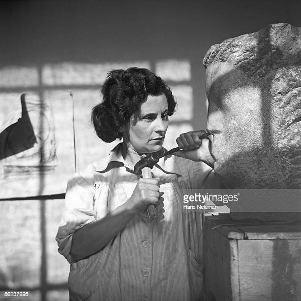 Portrait of Chilean sculptress Maria Fuentealba as she works on a large stone head at her atelier in the School of Fine Arts at the Museo Nacional de...