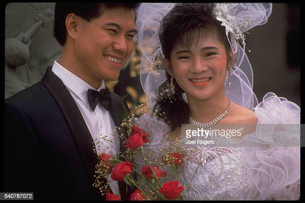 Portrait of Chinese bride and groom in western cloths with red roses Kuching sarawak Malaysia