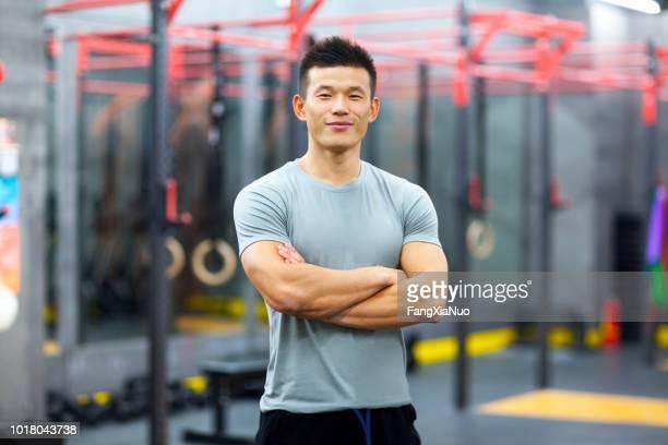 ジムで個人トレーナーの中国の肖像画 - コーチ ストックフォトと画像