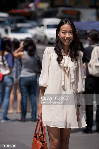 portrait of chinese woman on street smiling - mini dress stock pictures, royalty-free photos & images