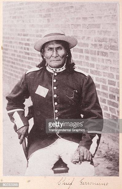 Portrait of Chiricahua Apache Geronimo as he sits on a chair near a brick wall dressed in a button coat and straw hat early 1900s
