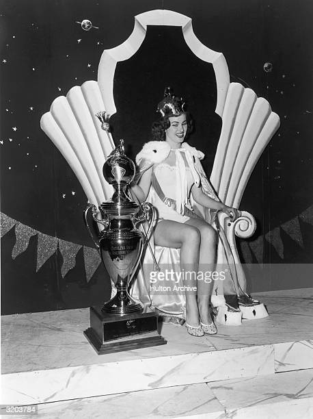 Portrait of Christiane Martel Miss Universe 1953 sitting on a throne and smiling while holding a scepter next to her trophy Long Beach California...