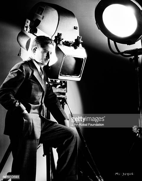 Portrait of cinematographer William H Daniels standing next to a large film camera for MGM Studios 1933