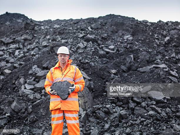 portrait of coal miner holding coal in surface coal mine - coal miner stock photos and pictures