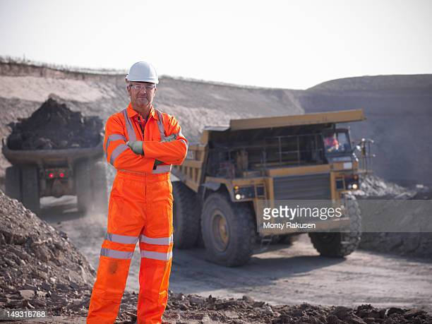 Portrait of coalminer with coal trucks in the background
