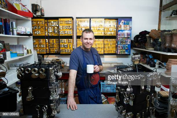 Portrait of cobbler and key cutter in his shop.