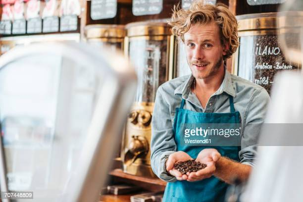 Portrait of coffee roaster in his shop holding coffee beans