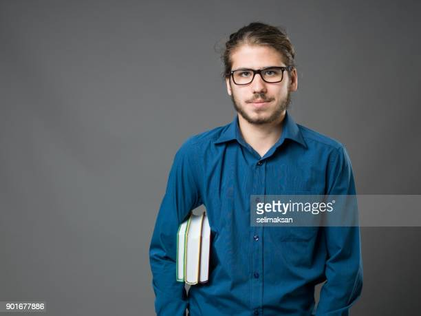 Portrait Of College Student Holding Books And Posing
