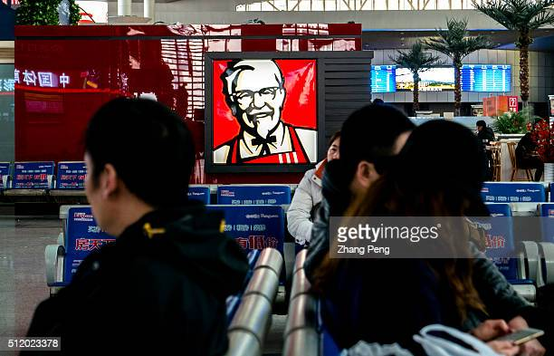 Portrait of Colonel Sanders hung on the exterior of a KFC restaurant in Tianjin railway station who looks at the passengers smiling On the early of...
