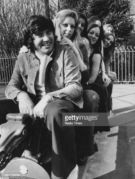 Portrait of comedian Jimmy Tarbuck and a row of models in a children's playground March 14th 1972