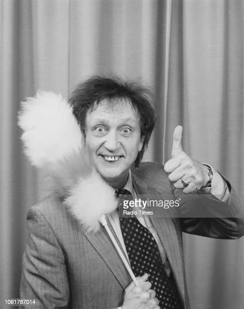 Portrait of comedian Ken Dodd with his feather duster, December 1986.