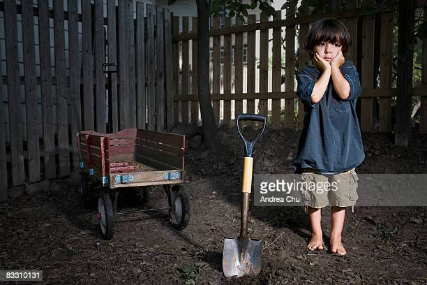 Portrait of concerned young boy with shovel.