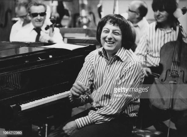 Portrait of conductor Andre Previn laughing as he sits at the piano May 15th 1974