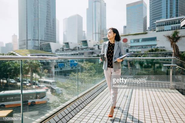 portrait of confidence asian businesswoman looking away and holding documents and having coffee to go against city scene in front of modern office buildings - zero waste stock pictures, royalty-free photos & images