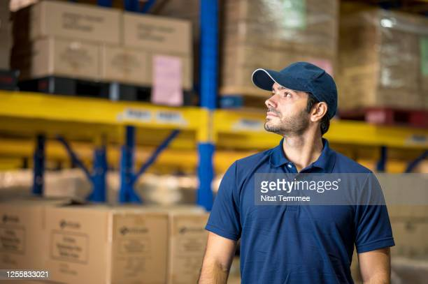 portrait of confidence caucasian warehouse worker wearing polo uniform working in distribution warehouse. looking away, front view. - polo shirt stock pictures, royalty-free photos & images