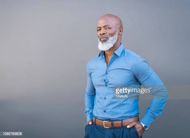 portrait of confident african american male against gray wall - completamente calvo foto e immagini stock