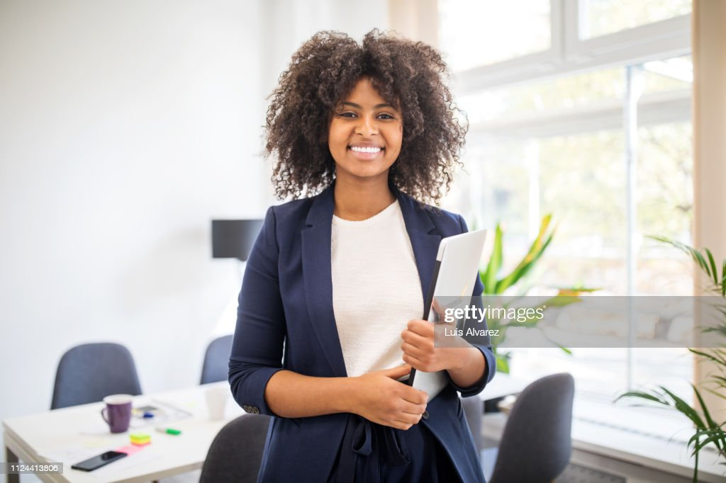 Portrait of confident african businesswoman with laptop : Stock Photo