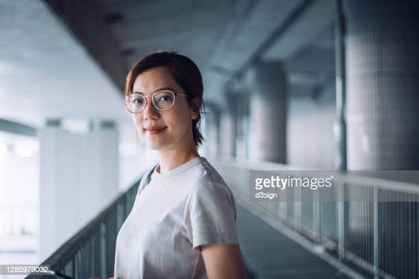 portrait of confident and successful young asian businesswoman looking at camera with smile, standing against urban bridge in the city - asia stock pictures, royalty-free photos & images