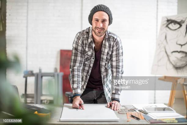 portrait of confident artist standing at his desk in studio - plaid shirt stock pictures, royalty-free photos & images