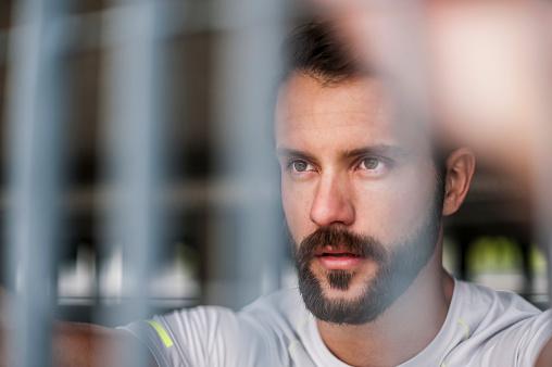 Portrait of confident athlete behind grid - gettyimageskorea