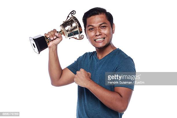 portrait of confident athlete holding trophy against white background - clenching teeth stock pictures, royalty-free photos & images