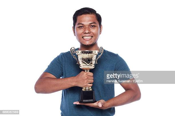 Portrait Of Confident Athlete Holding Trophy Against White Background