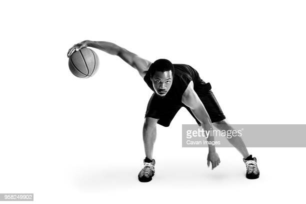 portrait of confident basketball player against white background - basketball player stock pictures, royalty-free photos & images