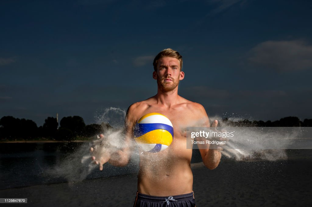 Portrait of confident beach volleyball player cleaning the ball : Stock-Foto