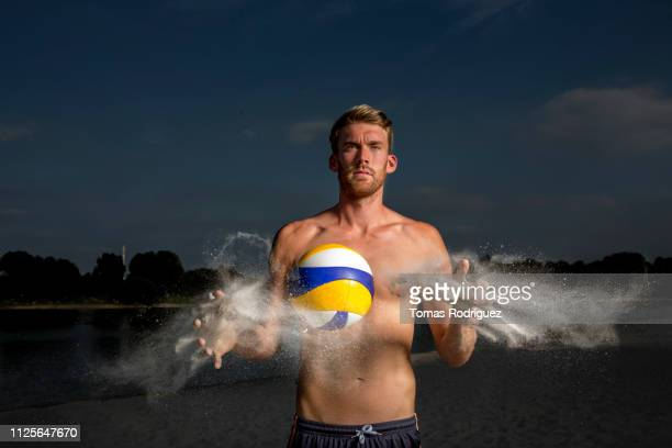 portrait of confident beach volleyball player cleaning the ball - strand volleyball der männer stock-fotos und bilder