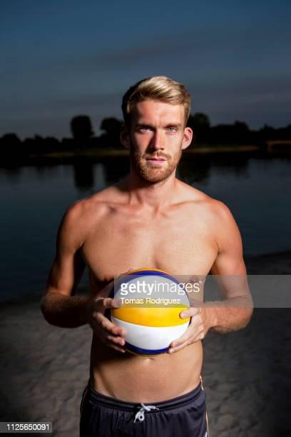 portrait of confident beach volleyball player holding the ball - strand volleyball der männer stock-fotos und bilder