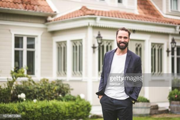portrait of confident bearded man with hands in pockets standing against villa - sakko stock-fotos und bilder