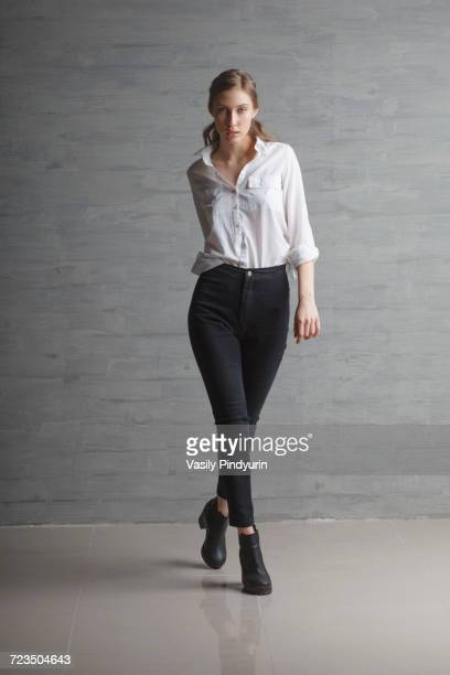 Portrait of confident beautiful fashion model walking against wall