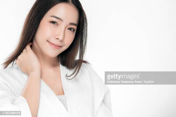 Portrait Of Confident Beautiful Woman Wearing Bathrobe Against White Background