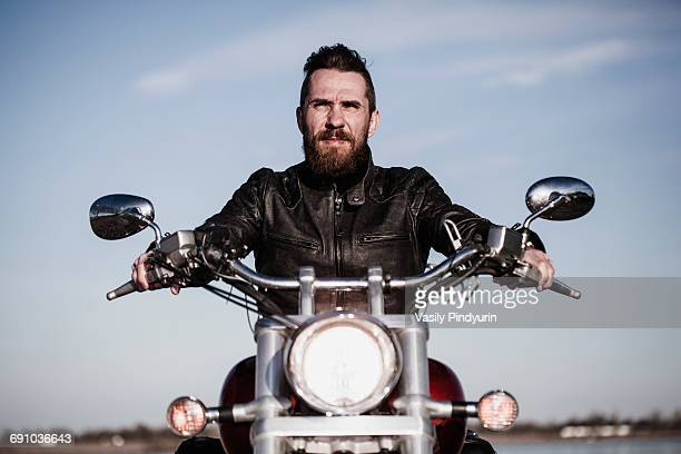 Portrait of confident biker sitting on motorcycle against sky