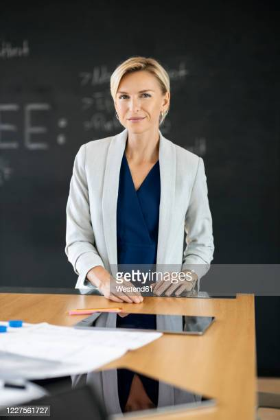 portrait of confident blond businesswoman in conference room with blackboard - mid adult stock pictures, royalty-free photos & images