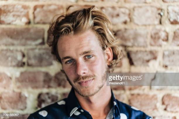 portrait of confident blond man at brick wall - cheveux blonds photos et images de collection