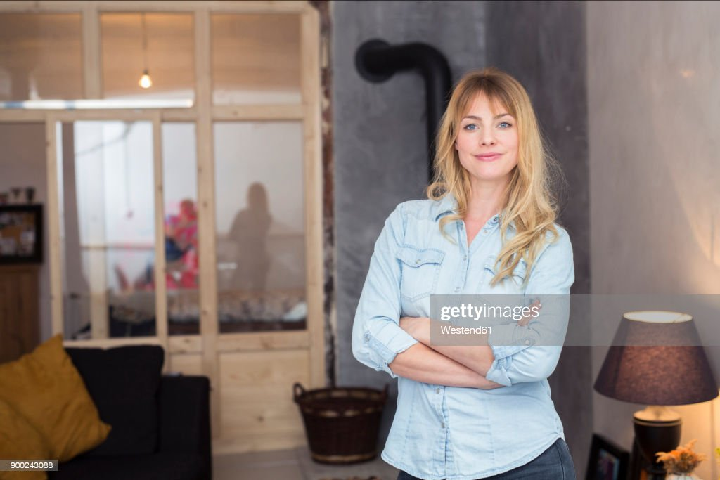 Portrait of confident blond woman at home : Stock Photo