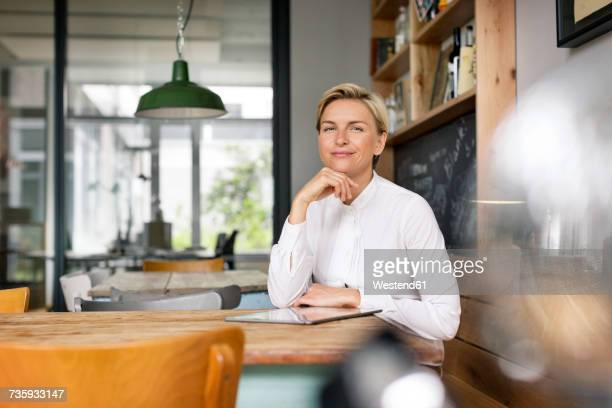 portrait of confident blond woman sitting at table - hand on chin stock pictures, royalty-free photos & images