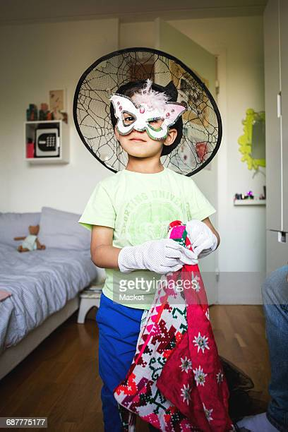 Portrait of confident boy in costume standing at home