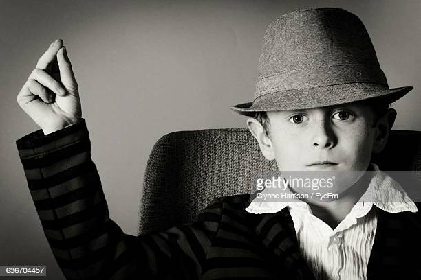Portrait Of Confident Boy In Hat While Snapping Fingers On Chair