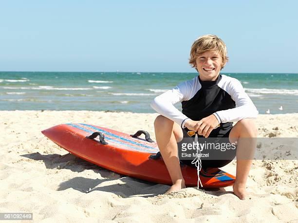 Portrait of confident boy nipper (child surf life savers) sitting on surfboard at beach, Altona, Melbourne, Australia