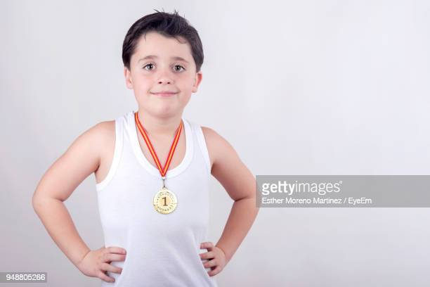 portrait of confident boy with hands on hip wearing medal against white background - medallist stock pictures, royalty-free photos & images