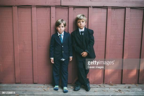 portrait of confident brothers wearing suits while standing against wooden wall - festlich gekleidet stock-fotos und bilder