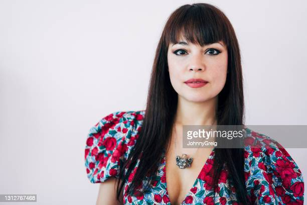 portrait of confident brunette woman in floral pattern dress - fringe dress stock pictures, royalty-free photos & images