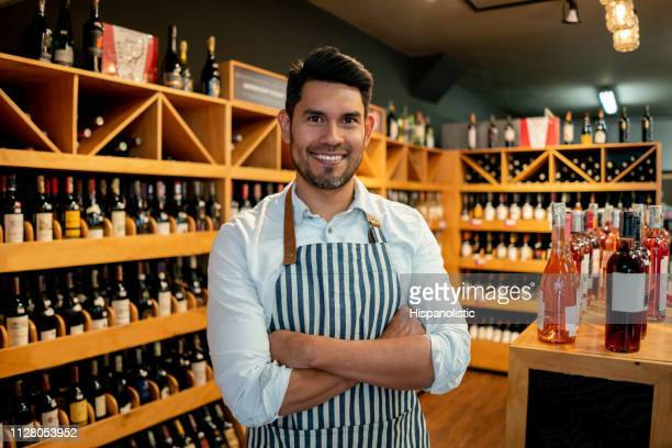 portrait of confident business owner of a wine cellar looking at camera smiling with arms crossed - liquor store stock pictures, royalty-free photos & images