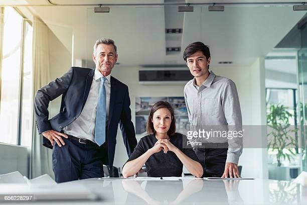 portrait of confident business people at desk - three people stock pictures, royalty-free photos & images