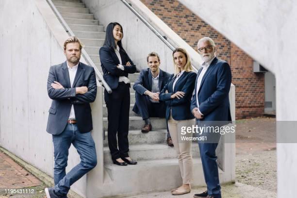portrait of confident business people on exterior stair - fünf personen stock-fotos und bilder