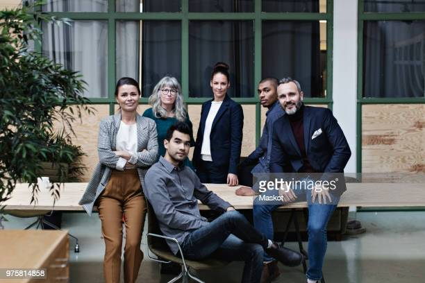 portrait of confident business team at table in creative office - middelgrote groep mensen stockfoto's en -beelden